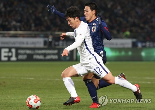 In this file photo taken on Dec. 16, 2017, South Korean defender Kim Min-woo (L in white) battles a Japanese player during their match at the East Asian Football Federation (EAFF) E-1 Football Championship at Ajinomoto Stadium in Tokyo. (Yonhap)