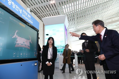 In this photo taken on Jan. 12, 2017, President Moon Jae-in points at an information bulletin at Incheon International Airport's second terminal during an event to celebrate the terminal's opening on Jan. 18. (Yonhap)