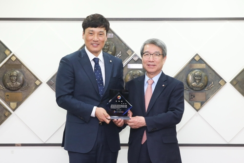 In this photo provided by the Korea Baseball Organization (KBO), retired star Lee Seung-yuop (L), the KBO's career home runs leader, and KBO Commissioner Chung Un-chan pose with a plaque appointing Lee as an honorary ambassador for the KBO. (Yonhap)