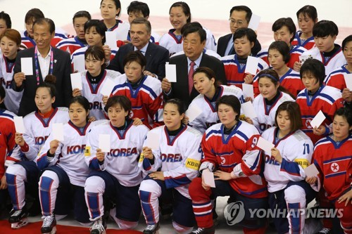 In this file photo taken April 6, 2017, members of the South Korean and North Korean women's hockey teams -- in white and red, respectively -- join for pictures after their game during the International Ice Hockey Federation World Championship Division II Group A tournament at Gangneung Hockey Centre in Gangneung, Gangwon Province. (Yonhap)
