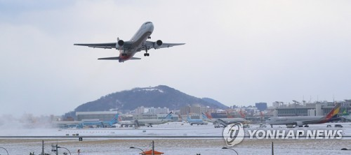 A plane takes off from Jeju International Airport on the southern resort island of Jeju on Jan. 12, 2018, after heavy snow and strong winds caused hundreds of flight cancellations and delays the previous day. (Yonhap)