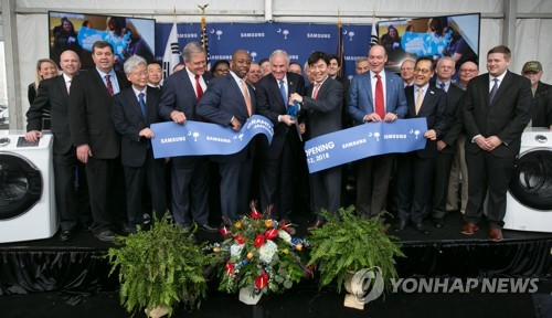 This photo, provided by Samsung Electronics Co., shows its company officials, including Kim Hyun-suk (5th from L), head of the consumer electronics division, and South Carolina Gov. Henry McMaster (4th from L), posing for a photo at the ceremony to mark the launch of operations at the firm's new plant in Newberry County, South Carolina, in the United States on Jan. 13, 2018. (Yonhap)