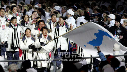 In this file photo taken Feb. 12, 2006, athletes from South and North Koreas march in together at the opening ceremony of the Torino Winter Olympics in Torino, Italy. South Korean speed skater Lee Bo-ra (front L) and North Korean figure skater Han Jong-in hold the Korean Unification Flag together. (Yonhap)