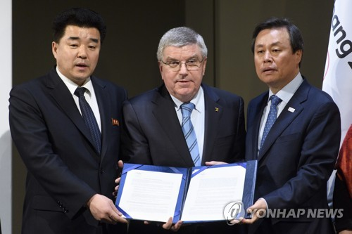 In this Associated Press photo taken Jan. 20, 2018, International Olympic Committee (IOC) President Thomas Bach (C), North Korean Sports Minister Kim Il-guk (L) and South Korean Sports Minister Do Jong-hwan hold up documents after a signing ceremony for the IOC's North and South Korean Olympic Participation Meeting at the IOC headquarters in Lausanne, Switzerland. (Yonhap)