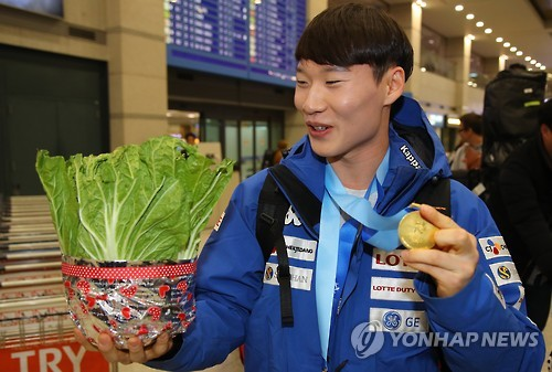 In this file photo taken Feb. 21, 2017, South Korean alpine snowboarder Lee Sang-ho holds a napa cabbage at Incheon International Airport after he returned home from the Asian Winter Games in Japan. (Yonhap)