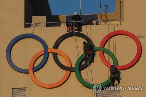 Workers install the Olympic Rings at Alpensia Ski Jumping Centre in PyeongChang, Gangwon Province, on Jan. 27, 2018. (Yonhap)
