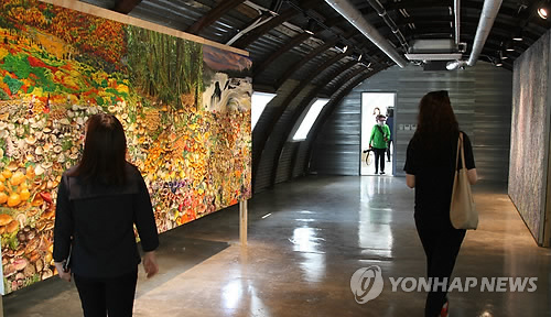 Visitors look around an exhibition held at the gallery of DMZ Camp 131 Greaves in Paju, Gyeonggi Province, on May 17, 2017. (Yonhap)