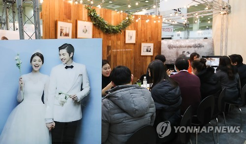 In this undated file photo soon-to-be married couples chat with wedding consultants. (Yonhap)