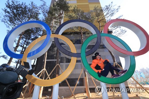 An athlete takes a photo of the Olympic Rings at Gangneung Olympic Village in Gangneung, Gangwon Province, on Feb. 6, 2018. (Yonhap)
