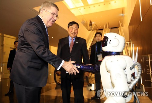 Thomas Bach, the head of the International Olympic Committee (IOC), shakes hands with a robot located at a hotel in Gangneung, around 230 kilometers east of Seoul, on Feb. 4, 2018. (Yonhap)