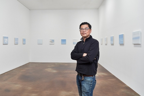 "Artist Byron Kim stands in front of his ""Sunday Paintings"" series in this photo provided by Kukje Gallery in Seoul on Feb.1, 2018. (Yonhap)"