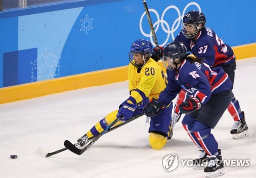 Park Chae-lin (C) and Randi Heesoo Griffin of Korea (R) battle Fanny Rask of Sweden for a loose puck during the teams' Group B game in the women's hockey tournament at the PyeongChang Winter Olympics at Kwandong Hockey Centre in Gangneung, Gangwon Province, on Feb. 12, 2018. (Yonhap)