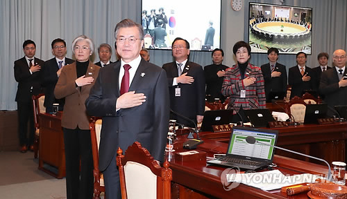 President Moon Jae-in (front) and other Cabinet members pledge allegiance to the flag ahead of a video conference at Cheong Wa Dae on Feb. 13, 2018. (Yonhap)