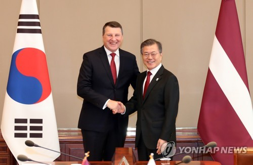 President Moon Jae-in (R) shakes hands with Latvian President Raimonds Vejonis during a meeting in Seoul on Feb. 13, 2018. (Yonhap)