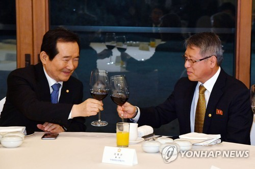 South Korea's National Assembly Speaker, Chung Sye-kyun (L), and Ri Yong-son, head of the International Taekwondo Federation, clink glasses during a dinner meeting at Chung's official residence in Seoul on Feb. 13, 2018. (Yonhap)