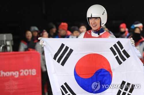 German-born South Korean luger Aileen Christina Frisch holds the South Korean national flag, taegeukgi, after finishing eighth in the women's singles at Olympic Sliding Centre in PyeongChang, Gangwon Province, on Feb. 13, 2018. (Yonhap)