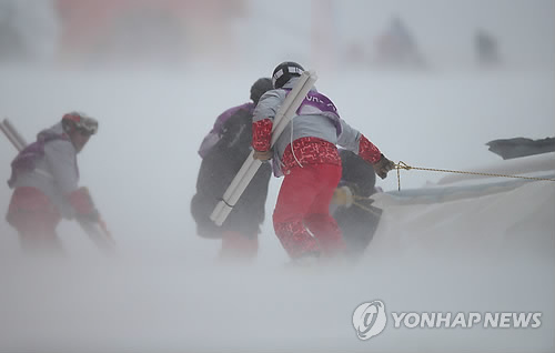 Volunteers and officials remove installed facilities at Yongpyong Alpine Centre in PyeongChang, Gangwon Province, on Feb. 14, 2018. The women's alpine slalom event was moved to Feb. 16 due to bad weather. (Yonhap)