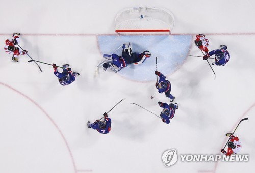 Korean players try to stop Japan from scoring in Group B game of the women's hockey tournament at the Pyeong Chang Winter Olympics at Kwandong Hockey Centre in Gangneung Gangwon Province on Feb. 14 2018