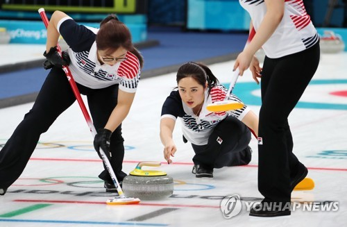 South Korean curler Kim Kyeong-ae (C) throws a stone during her team's round robin match against China at Gangneung Curling Centre in Gangneung, Gangwon Province, on Feb. 18, 2018. (Yonhap)