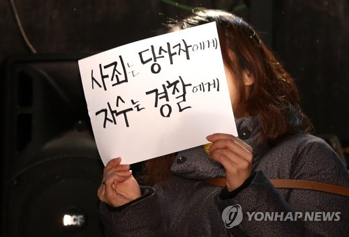 A woman holds a banner reading, 'Apologize to the party concerned, surrender to the police' during a press conference for theatrical director Lee Youn-taek in Seoul on Feb. 19, 2018. (Yonhap)
