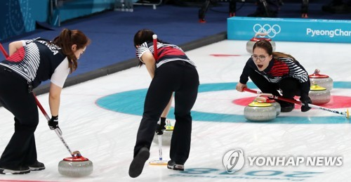 South Korean curlers sweep the ice sheet in the Pyeong Chang Winter Games women's curling semifinals against Japan at the Gangneung Curling Centre on Feb. 23 2018