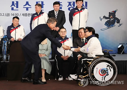 South Korean President Moon Jae-in (L) shakes hands with wheelchair curler Bang Min-ja during the South Korean squad launch ceremony for the PyeongChang Paralympics in Seoul on March 2, 2018. (Yonhap)