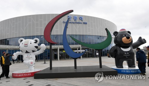 "Three ""agitos"" forming the emblem of the Paralympic Games are displayed between the PyeongChang Paralympics mascot Bandabi (R) and the PyeongChang Olympics mascot Soohorang at Gangneung Station in Gangneung, Gangwon Province, on March 6, 2018. (Yonhap)"