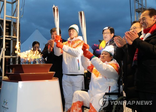 South Korean skeleton slider Yun Sung-bin (2nd from L) holds the torch during the torch relay for the PyeongChang Paralympic Games in Chuncheon, Gangwon Province, on March 5, 2018. (Yonhap)