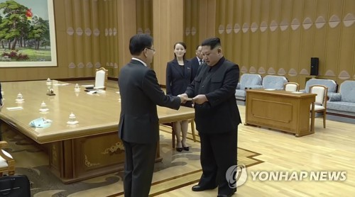 Footage aired by North Korea's state television shows North Korean leader Kim Jong-un (R) receiving a personal letter from South Korean President Moon Jae-in through Moon's top envoy, Chung Eui-yong, at a building in Pyongyang on March 6, 2018. (Yonhap)