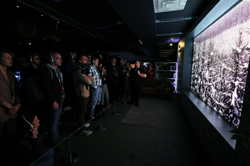 Visitors look at a Samsung Electronics Co.'s premium TV during a showcase event held in New York, the United States, in this photo released by the company on March 8, 2018. (Yonhap)