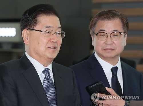 Chung Eui-yong (L), South Korean President Moon Jae-in's top security adviser, speaks to reporters at Seoul's Incheon International Airport before he and Suh Hoon (R), chief of the National Intelligence Service, embarked on a three-day visit to Washington on March 8, 2018. (Yonhap)