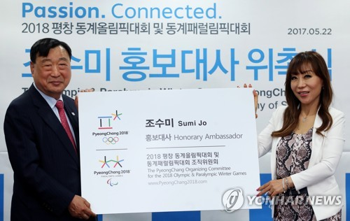 Soprano Sumi Jo (R) poses with Lee Hee-beom, president of the organizing committee for the 2018 PyeongChang Winter Olympics, after being named an honorary ambassador for PyeongChang in Seoul on May 22, 2017. (Yonhap)