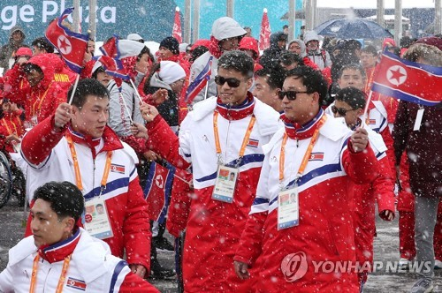 North Korean athletes and officials for the PyeongChang Winter Paralympics wave their national flag during the welcome ceremony at the athletes' village in PyeongChang, Gangwon Province, on March 8, 2018. (Yonhap)