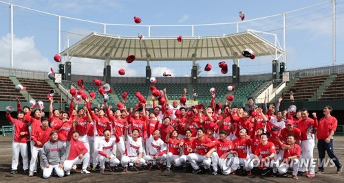 This photo provided by the Kia Tigers baseball club shows the players and coaches throwing their hats in the air at the end of their spring training in Okinawa, Japan, on March 7, 2018. (Yonhap)