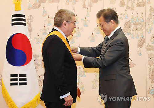 South Korean President Moon Jae-in (R) confers the Cheongryong Medal, the country's highest decoration in the Order of Sport Merit, on International Olympic Committee President Thomas Bach in a ceremony at the presidential office Cheong Wa Dae in Seoul on March 8, 2018. (Yonhap)