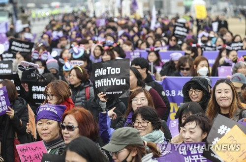 "In this file photo, participants in the 34th Korean Women's Conference march in the streets in downtown Seoul on March 4, 2018, while holding up ""Me Too"" and ""With You"" signs. The event was held to mark the U.N.-designated International Women's Day. (Yonhap)"