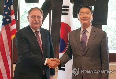 In this photo provided by the foreign ministry, South Korea's chief negotiator, Chang Won-sam (R), shakes hands with his U.S. counterpart, Timothy Betts, in Honolulu, Hawaii, on March 7, 2018. (Yonhap)