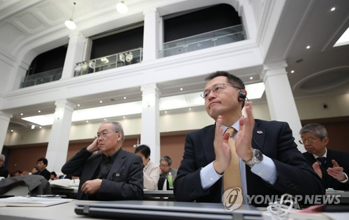 Japanese participants clap as South Korean pastor Ham Sei-ung gives a welcoming address during a meeting to discuss peace on the Korean Peninsula and the protection of Japan's peace constitution at the Citizens&apos Hall of Seoul City Hall on March