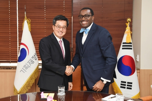 South Korea's finance minister Kim Dong-yeon (L) shakes hands with Akinwumi Adesina, president of the African Development Bank (AfDB) in Seoul, on March 13, 2018. (Yonhap)