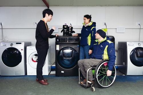 Participants in the PyeongChang Winter Paralympics receive instructions on using Samsung Electronics Co.'s washers at the athletes' village in PyeongChang, around 180 kilometers east of Seoul, in this photo released by Samsung on March 14, 2018. (Yonhap)
