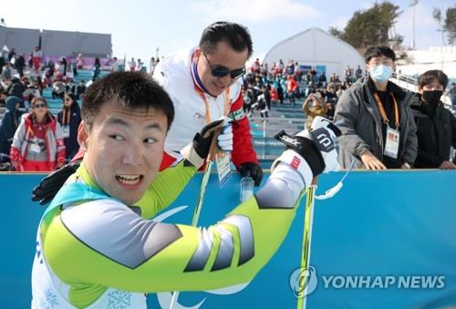 North Korea's Kim Jong-hyon (L) watches his time after finishing the men's 1.1 kilometer sprint sitting cross-country skiing event of the PyeongChang Winter Paralympics at Alpensia Biathlon Centre in PyeongChang, Gangwon Province, on March 14, 2018. (Yonhap)