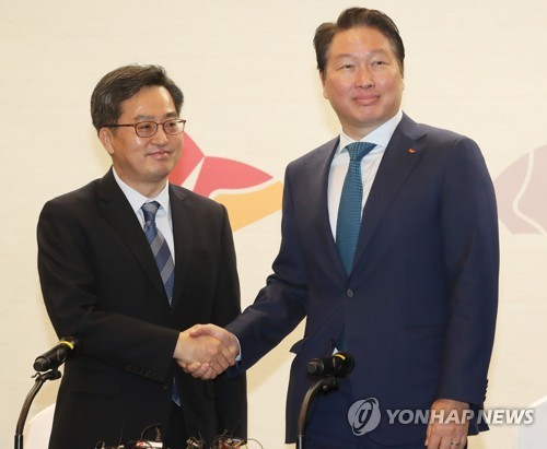 Finance Minister Kim Dong-yeon (L) shakes hands with Chey Tae-won, chairman of SK Group, before a meeting in Seoul on March 14, 2018. (Yonhap)