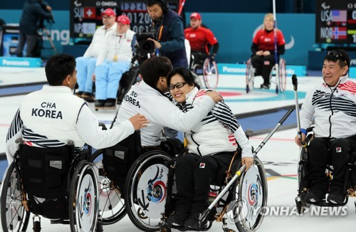 South Korean wheelchair curlers celebrate after beating Britain 5-4 in a round-robin match at the Pyeong Chang Winter Paralympics at Gangneung Curling Centre in Gangneung Gangwon Province