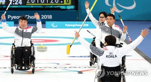 South Korean wheelchair curlers celebrate after beating China 7-6 in a round-robin match at the Pyeong Chang Winter Paralympics at Gangneung Curling Centre in Gangneung Gangwon Province