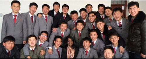This photo captured from the website of Pyongyang University of Science & Technology on March 16, 2018, shows North Korean students posing happily with a foreign teacher. (Yonhap)