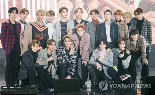 """In this file photo, NCT pose for photos at a media showcase for its album, """"NCT 2018 Empathy,"""" at Korea University's Hwajung Gymnasium in Seoul on March 14, 2018. (Yonhap)"""
