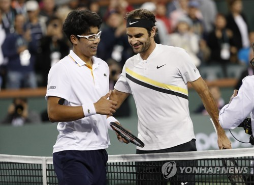 Chung Hyeon of South Korea shakes hands with Roger Federer of Switzerland after losing in straight sets in the quarterfinals at the BNP Paribas Open at Indian Wells Tennis Garden in Indian Wells California