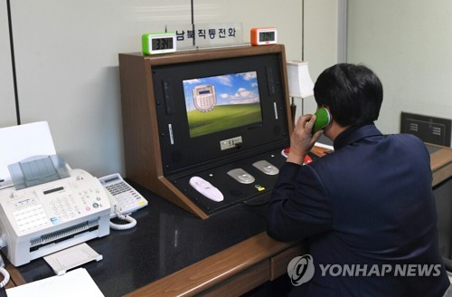 This photo, provided by South Korea's unification ministry on Jan. 3, 2018, shows a South Korean liaison official using a border communication hotline to communicate with his North Korean counterpart. (Yonhap)