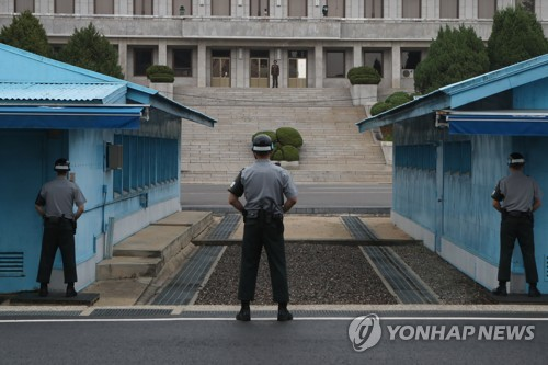 This file photo shows South and North Korean guards standing face-to-face at the Joint Security Area (JSA), a small strip of land of the truce village of Panmunjom. (Yonhap)
