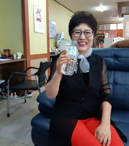 In this photo taken March 29, 2018, and provided by her, Roh Hyeon-young, a 61-year-old saleswoman, enjoys a bottle of deep sea drinking water at an outlet of home-grown direct selling company Atomy Co. in Daegu, about 300km south of Seoul. (Yonhap)